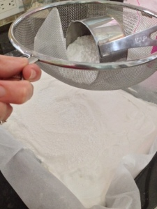 Sifting powdered sugar on top of marshmallows
